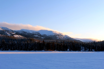 Frozen lake with mountains in the background.